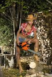 Girl with a chainsaw. In the autumn garden Stock Photography