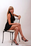 Girl on a chair. Girl in a black dress on a chair Stock Photography