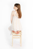 Girl on a chair. Girl sitting on a wooden chair, legs crossed Royalty Free Stock Image