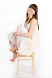 Girl on a chair. Girl sitting on a wooden chair, legs crossed Stock Photos