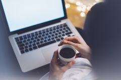 Girl in a chair in a homely atmosphere with an open laptop with a empty blank screen monitor and a cup of coffee or tea. On the background bokeh light stock photography