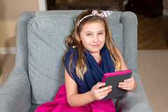 Girl in a Chair with a Tablet Stock Images