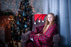 Girl in chair wrapped in a blanket, background of Christmas tree Stock Photography