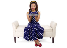 Girl on Chaise with Empty Tray. Young black girl holding an empty tray sitting on a chaise lounge stock images