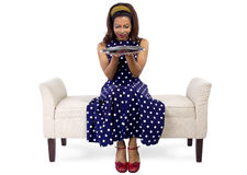 Girl on Chaise with Empty Tray. Young black girl holding an empty tray sitting on a chaise lounge royalty free stock photo