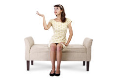 Girl on Chaise Lounge Advertising. Stylish retro female sitting on a chaise lounge or sofa on white background stock photography
