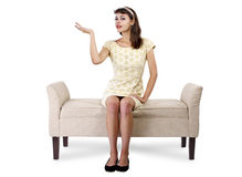 Girl on Chaise Lounge Advertising. Stylish retro female sitting on a chaise lounge or sofa on white background stock photo