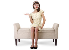 Girl on Chaise Lounge Advertising. Stylish retro female sitting on a chaise lounge or sofa on white background stock image