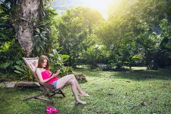 Girl in a chaise lounge. Girl sitting reading a book in a deck chair in a tropical garden, Brazil stock photography