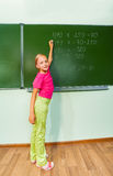 Girl with chalk in hand writing equation Royalty Free Stock Photography