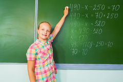 Girl with chalk writing mathematics equation Stock Photo