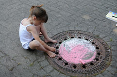 Girl chalking the street Royalty Free Stock Photography