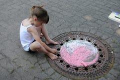 Girl chalking the street