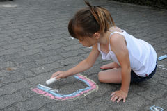 Girl chalking the street Stock Photography