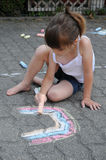 Girl chalking the street Royalty Free Stock Images