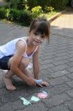 Girl chalking the street Stock Image