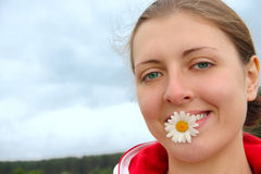 The girl with chamomile in teeth. The girl on summer meadow with chamomile in teeth Stock Photos