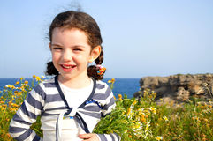 Little girl with chamomiles againdt the sea Royalty Free Stock Photos