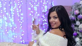 Girl with champagne near Christmas tree, close-up. Portrait of sexy girl with long dark hair with a glass of champagne on the background of decorated Christmas stock video