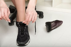 The girl changes footwear at office at the end of the working day Stock Images