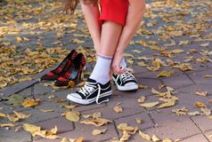 Girl changes shoes for sneakers royalty free stock image