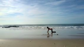 Girl Changes Yoga Poses on Beach at Flowing Waves. Girl with ponytail changes yoga poses on tropical ocean beach against soft flowing waves and boundless blue stock video