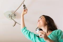 Girl changing light bulb Stock Photo