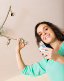 Girl changing light bulb Royalty Free Stock Photography