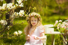 Girl in chaplet. Little girl in spring garden with blooming trees wearing a chaplet Stock Photos