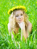 Girl in chaplet lying at meadow Royalty Free Stock Images