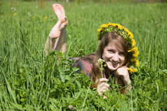 Girl in a chaplet lying from meadow. Long-haired teen girl in a chaplet lying from meadow Royalty Free Stock Images