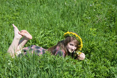 Girl in a chaplet lying from meadow. Barefoot teen girl in a chaplet lying from meadow Stock Photos