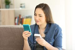 Girl charging a smart phone with a portable charger. Sitting on a couch in the living room at home Stock Photo