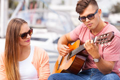 Girl charmed by musican. Love romance affection music sound talent concept. Girl charmed by musican. Young guitarist playing on instrument in port Royalty Free Stock Photo