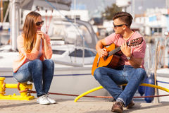 Girl charmed by musican. Love romance affection music sound talent concept. Girl charmed by musican. Young guitarist playing on instrument in port Royalty Free Stock Images