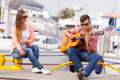 Girl charmed by musican. Love romance affection music sound talent concept. Girl charmed by musican. Young guitarist playing on instrument in port Stock Photos