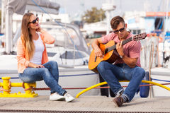 Girl charmed by musican. Love romance affection music sound talent concept. Girl charmed by musican. Young guitarist playing on instrument in port Stock Photo