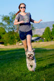 Girl chasing little dog. Young teen girl chasing a small scruffy dog Royalty Free Stock Photos
