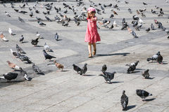 Girl chasing pigeons on urban square in Athens. Travel to Greece - girl chasing pigeons on urban square in Athens city Royalty Free Stock Photo