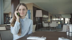Girl check and talk on a phone by the window stock video