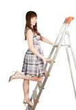 Girl in checked dress on stepladder Stock Image