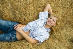 Girl in checked shirt resting on hay Royalty Free Stock Photography