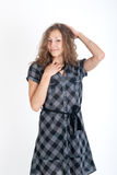 Girl in a checkered dress Stock Images