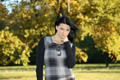 Girl in checkered dress in autumn park. Girl in checkered dress with flying hair in autumn park Stock Photos