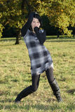 Girl in checkered dress posing in autumn park Royalty Free Stock Image