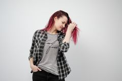 The girl in a plaid gray shirt on a white background with dyed red hair. A girl in a checkered gray shirt on a white background with dyed red hair, laughing and stock photos