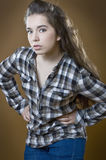 Girl in checkered shirt on brown (orange) background. Studio photography on a light brown (orange) background Stock Photo