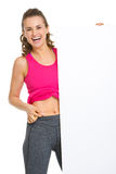 Girl checking body fat and showing blank billboard Stock Images