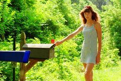 Girl Checking Mail. Pretty girl checking mail box for mail stock photo