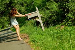 Girl Checking Mail. Pretty girl checking mail box for mail royalty free stock photo
